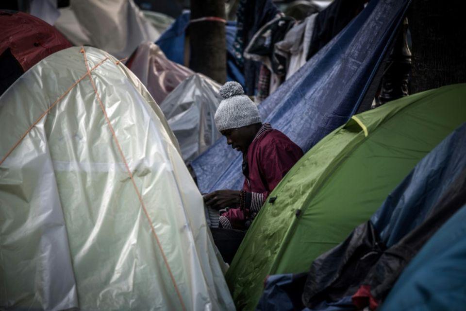 1067570-un-migrant-assis-au-milieu-de-tentes-plantees-dans-une-rue-de-paris-le-27-octobre-2016